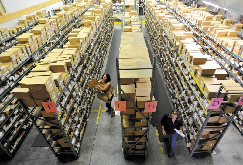 Workers at Johnny's Selected Seeds in Winslow sort packages at the shipping center. The company reports strong growth and has created four new positions.