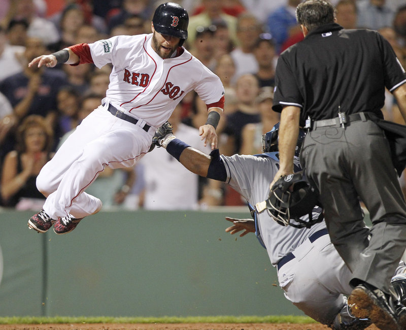 Dustin Pedroia is tagged out by Tampa Bay's Jose Molina on Saturday night. The Red Sox had the last laugh, as Jarrod Saltalamacchia hit a ninth-inning home run for a 3-2 win.