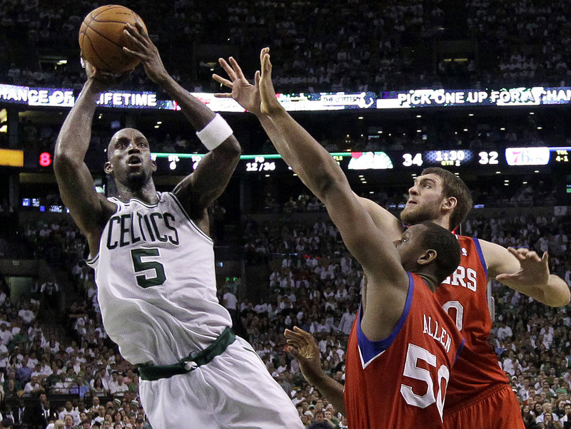 Kevin Garnett of the Boston Celtics shoots over Lavoy Allen, 50, and Spencer Hawes of the Philadelphia 76ers during Boston's 85-75 victory.