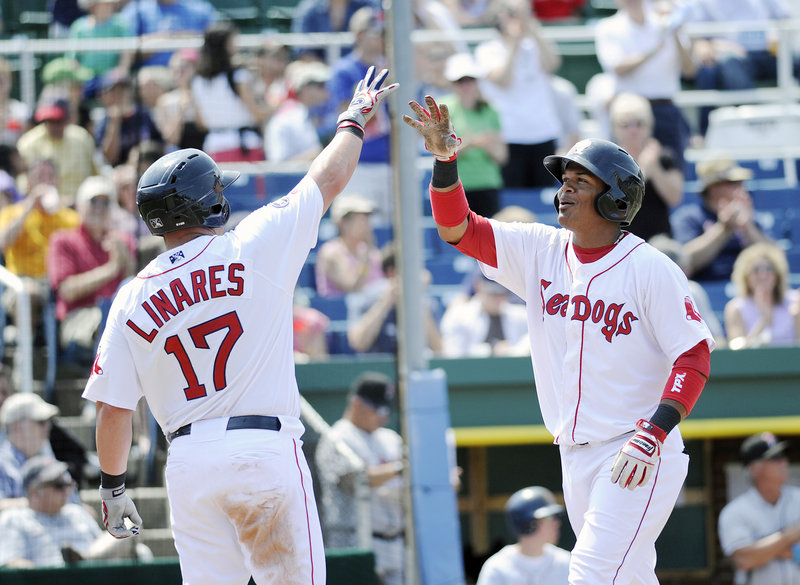 Juan Carlos Linares, left, greets Reynaldo Rodriguez after Rodriguez hit a two-run home run in the fourth inning Sunday. Rodriguez also had a pair of doubles in the 8-5 win over New Britain.