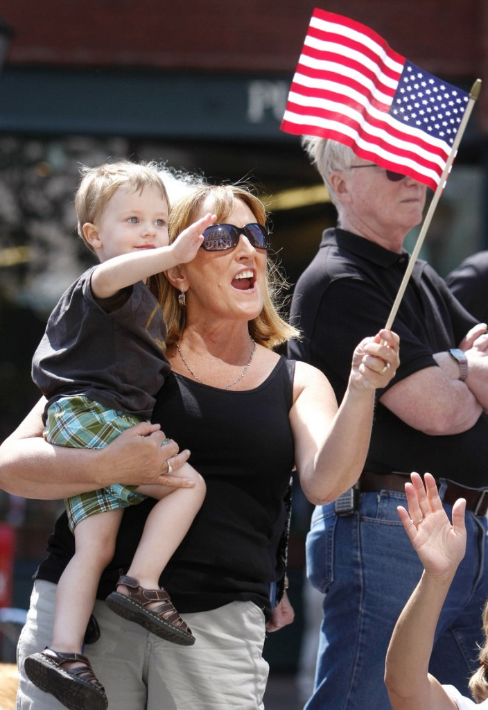 Pam Grant of Portland holds her nephew Cameron Toher, 3, also of Portland, as they enjoy the parade along Congress Street on Monday.