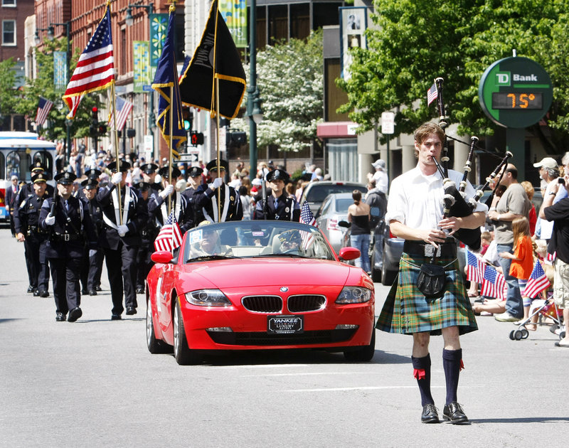 Bagpiper Aaron Seale of South Portland leads the Memorial Day parade down Congress Street. Parade grand marshal John S. Hammonds, a Navy veteran of World War II, follows in the red car.