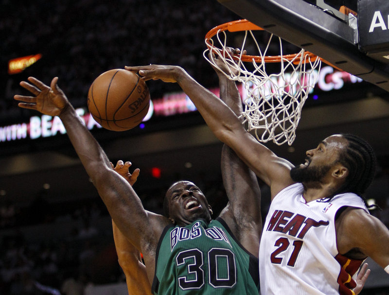 Brandon Bass gets his shot blocked by Miami's Ronny Turiaf, one of 11 blocked shots for the Heat in their 93-79 win over the Celtics.