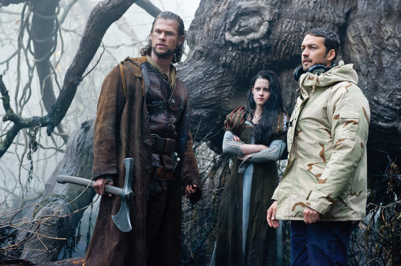 "Chris Hemsworth, left, as the Huntsman, and Kristen Stewart as Snow White with director Rupert Sanders on the set of ""Snow White and the Huntsman."""