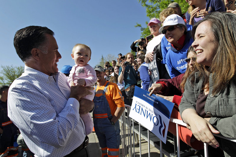 Mitt Romney holds a baby as he greets supporters after speaking at a campaign event Tuesday in Craig, Colo.