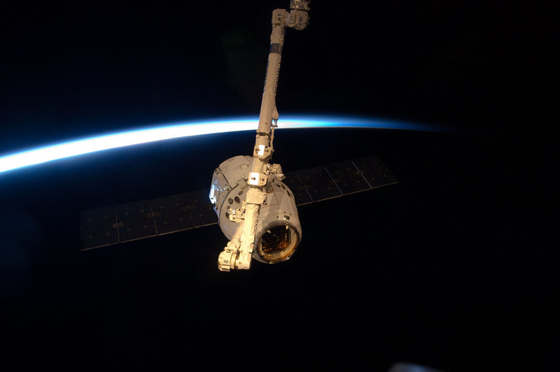 With a thin line of Earth's atmosphere forming a backdrop, the SpaceX Dragon commercial cargo craft is grappled by a robotic arm at the International Space Station last Friday. It was due to return to Earth today, carrying back old equipment and experiments.