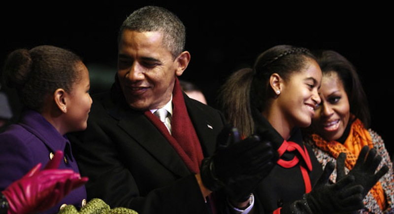In this December 2011 photo, President Barack Obama spends time with his wife, Michelle, and daughters Sasha and Malia. Obama is attempting to woo Hispanic voters in part with Spanish-language commercials focusing on his image as a strong family man.