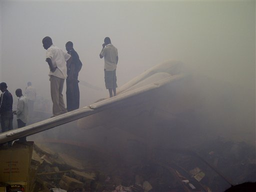 Onlookers stand on the tail wing of a crashed passenger plane in a neighborhood just north of Murtala Muhammed International Airport, in Lagos, Nigeria, today.