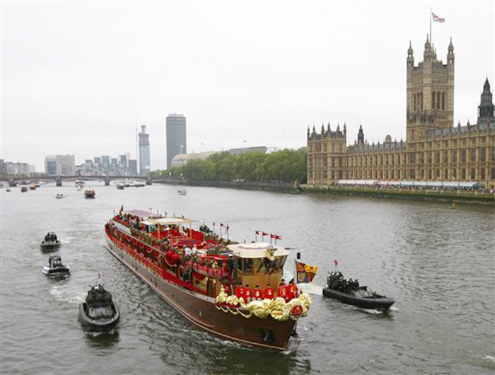 The Royal Barge is seen passing the Houses of Parliament during the Thames Diamond Jubilee River Pageant in London, Sunday, June 3, 2012. More than 1,000 boats were to sail down the Thames on Sunday in a flotilla tribute to Queen Elizabeth II's 60 years on the throne that organizers are calling the biggest gathering on the river for 350 years. Despite cool, drizzly weather, hundreds of thousands of people are expected to line the riverbanks in London, feting the British monarch whose longevity has given her the status of the nation's favorite grandmother. (AP Photo/Tim Hales)