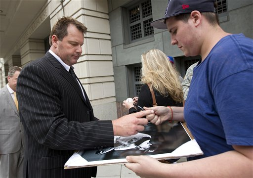 Former Major League Baseball pitcher Roger Clemens, left, signs autographs as he leave federal court in Washington on Monday.