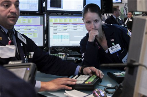 Frank Babino, left, and Amanda Anderson, right, work on the floor of the New York Stock Exchange on Wednesday, June 6, 2012. A 200-point charge turned the Dow Jones industrial average positive for the year following a dismal stretch in May. (AP Photo/Bebeto Matthews)