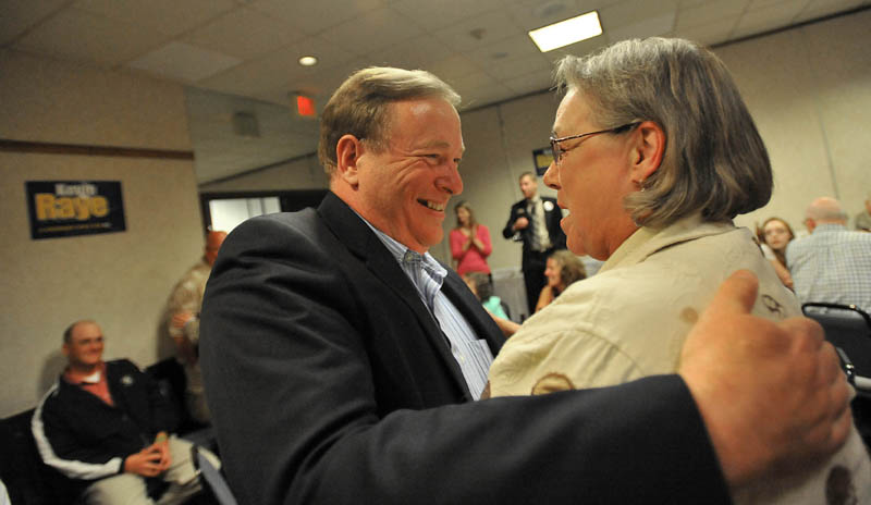 Staff photo by Michael G. Seamans Kevin Raye, candidate for US second congressional district, greets supporter Gail Kelly at the Ramada Inn in Bangor Tuesday night.