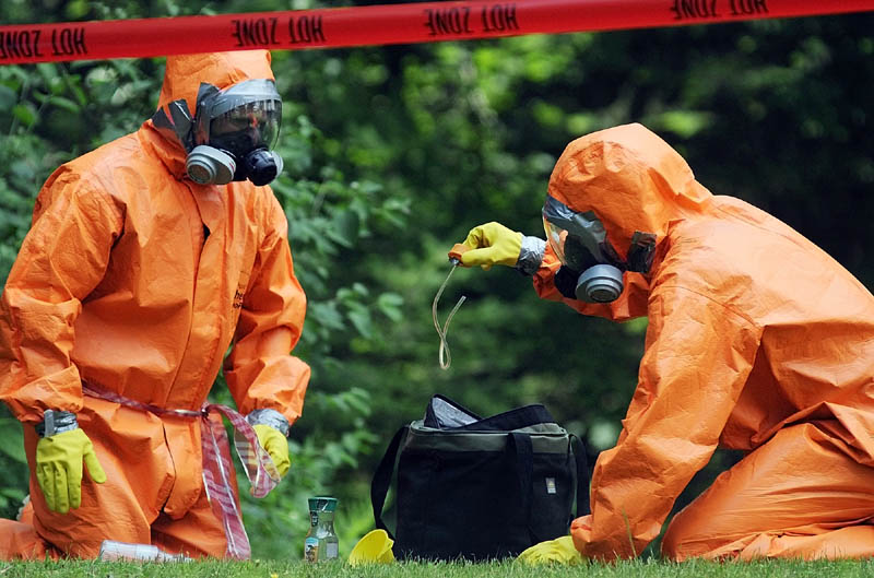HOT ZONE: Maine Drug Enforcement Agents inspect items they collected Thursday behind a home on Cressey Road in Monmouth, where three men were arrested Wednesday during an investigation of an alleged methamphetamine lab. Agents donned hazardous material suits in 90 degree heat while collecting evidence at the trailer for several hours.