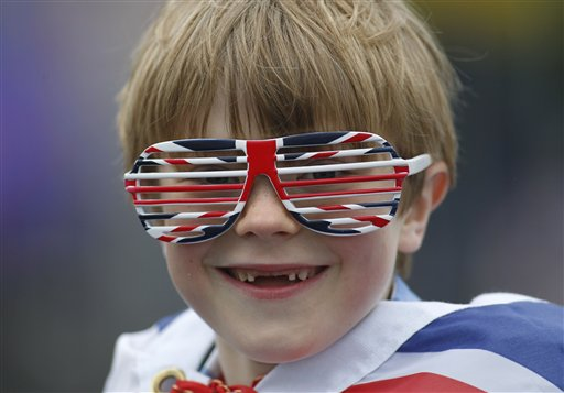 Owen Lewis, 7, is among thousands of people gathering along the river Thames in London waiting for Britain's Queen Elizabeth II flotilla of boats to sail past.