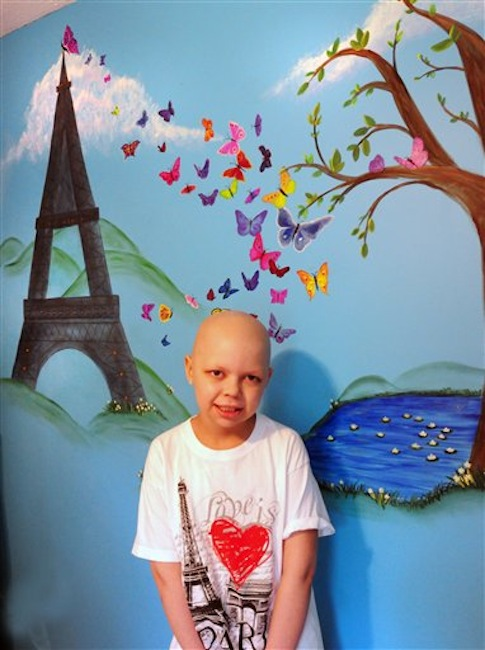 In this May 15, 2012 photo, Emma Jouneay, 9, poses in her bedroom by a mural that includes the Eiffel Tower in Merrimac, Mass. Jouneay, who was diagnosed with stage IV neuroblastoma, has collected souvenirs from 46 countries, 50 states and all the continents, through Emma's Pen Pal Adventure Around the World, born on Facebook in November. (AP Photo/Newburyport Daily News, Bryan Eaton)