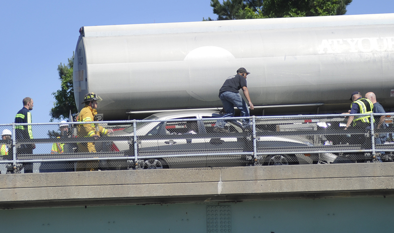 Crews work to remove a car wedged between a tractor-trailer and the guardrail on I-295 today.