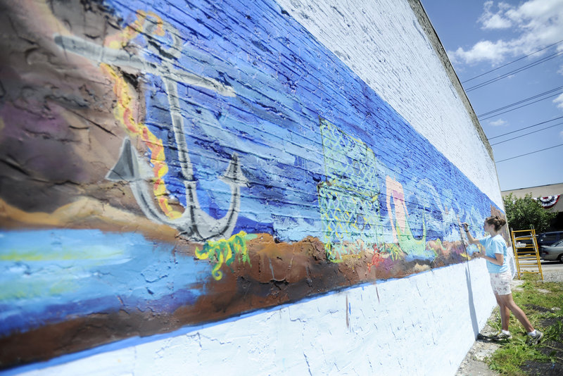Noelle Webster, a Cape Elizabeth High School senior, paints a mural on the exterior wall of The 50's Pub in downtown Biddeford Thursday. Webster, who is planning to attend Rhode Island School of Design in the fall, is creating the mural as part of a graduation service requirement.