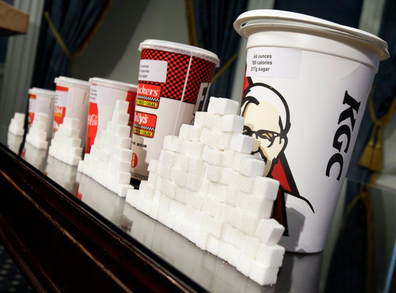 Drink cups and sugar cubes are displayed Thursday at New York City Hall, where Mayor Michael Bloomberg proposed a ban on sales of large sodas and other sugary drinks in city eateries and movie theaters.