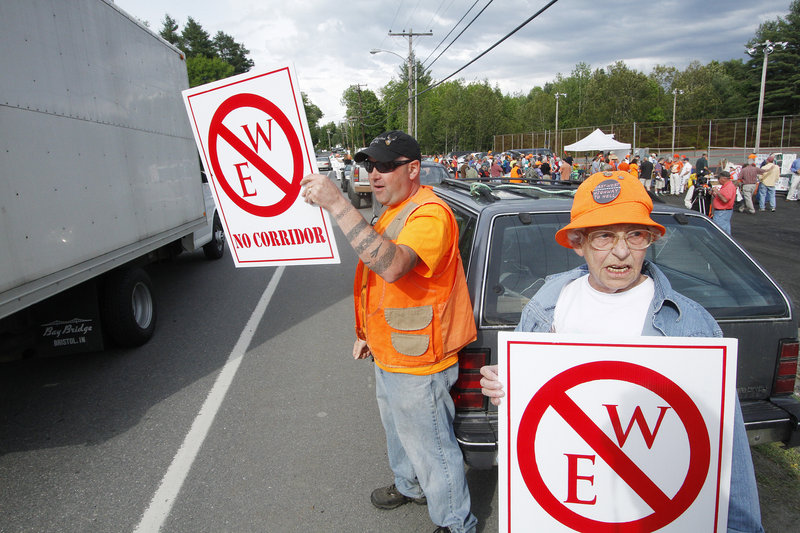 Rob Borden and Erla St. Pierre protest the proposed East-West Highway before a public meeting in Dover-Foxcroft on May 31.