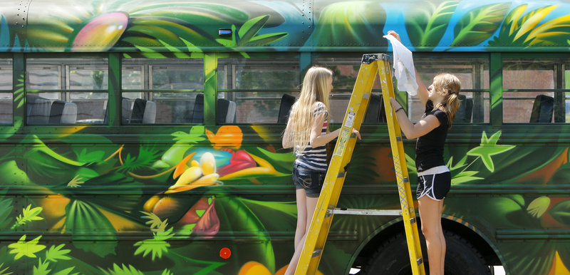 Elsie Parrot, left, and Annabelle Carter clean a bus that Breakwater School students painted under the direction of Tim Clorius, an artist in residence. The jungle theme was inspired by eighth-graders' trip to Costa Rica. The buses were parked in front of the Space gallery in Portland on Friday night.