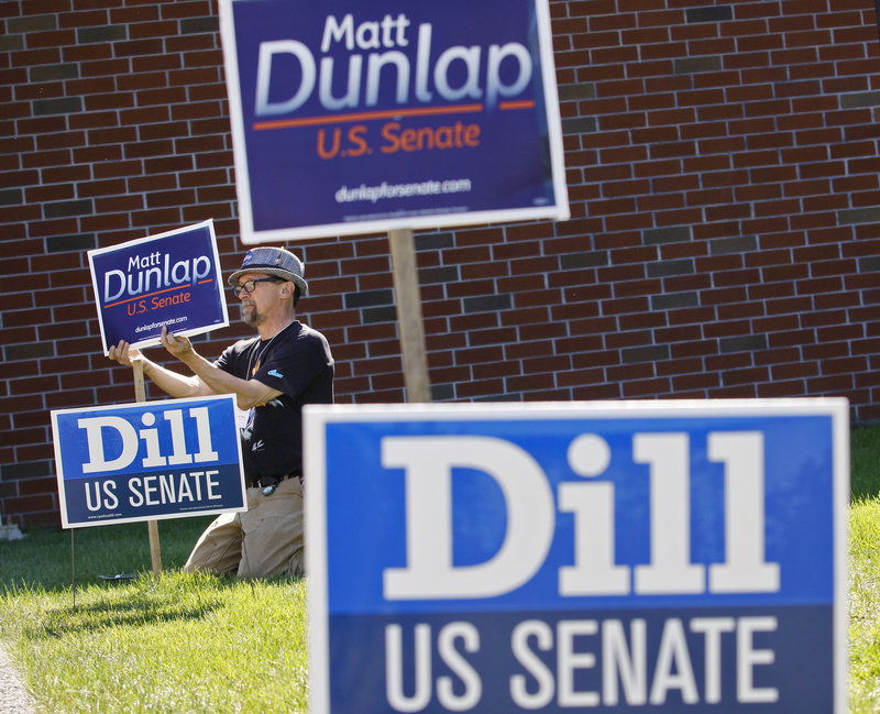 Robert O'Brien of Peaks Island, a campaign worker for U.S. Senate candidate Matt Dunlap, puts up signs before the Democratic convention at the Augusta Civic Center on Friday. Democrats are vowing to reverse losses in the 2010 elections with victories this fall.