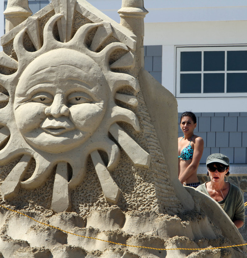 Darlene Grady Duggan puts the finishing touches on a sand sculpture Friday in front of the newly renovated Seashell entertainment complex and visitor center at Hampton Beach in Hampton, N.H.