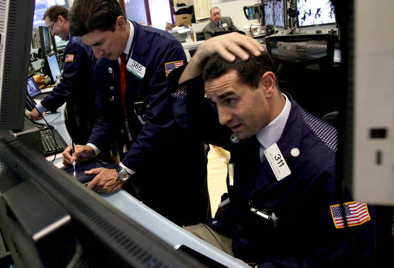 Trader Michael Liloia, right, works at the New York Stock Exchange on Friday, when markets slid back by more than 2 percent.