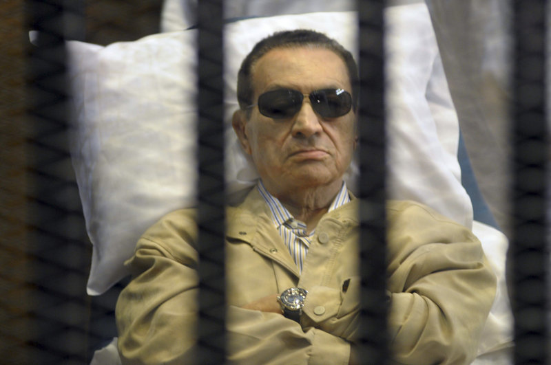 Egypt's former President Hosni Mubarak lies on a gurney inside a barred cage at a courthouse in Cairo on Saturday.