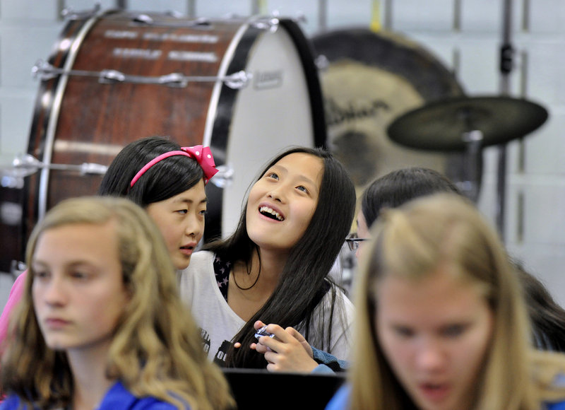 Hu Yanjie looks up while laughing at photos taken by one some of her classmates from China while sitting in on a band class Monday at Falmouth Middle School. Falmouth students acted as tour guides and classroom buddies for their guests.