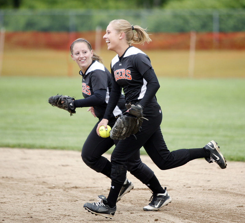 Kristina McCurry, left, and Mariah Albert of Biddeford share a laugh Tuesday after Albert made a tough catch in right field to end an inning. The defense helped the Tigers preserve a 2-0 victory and advance to the quarterfinals of the Western Class A softball tournament.
