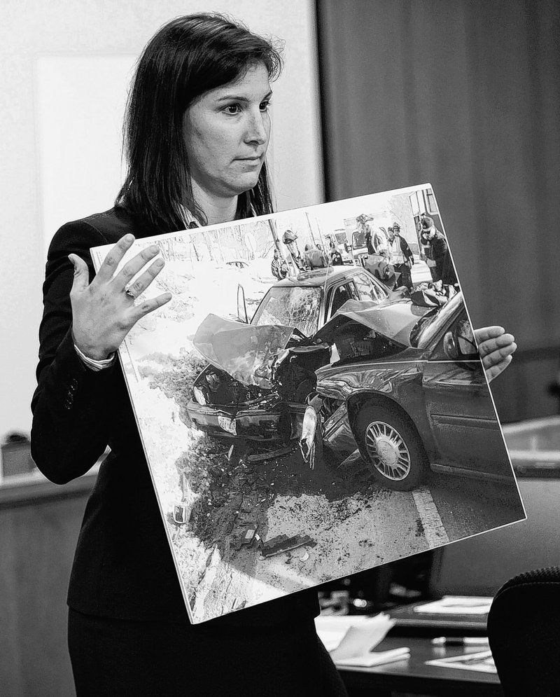 The prosecutor shows jurors a photograph from the auto crash during the trial of Aaron Deveau, above, in Haverhill District Court Tuesday.