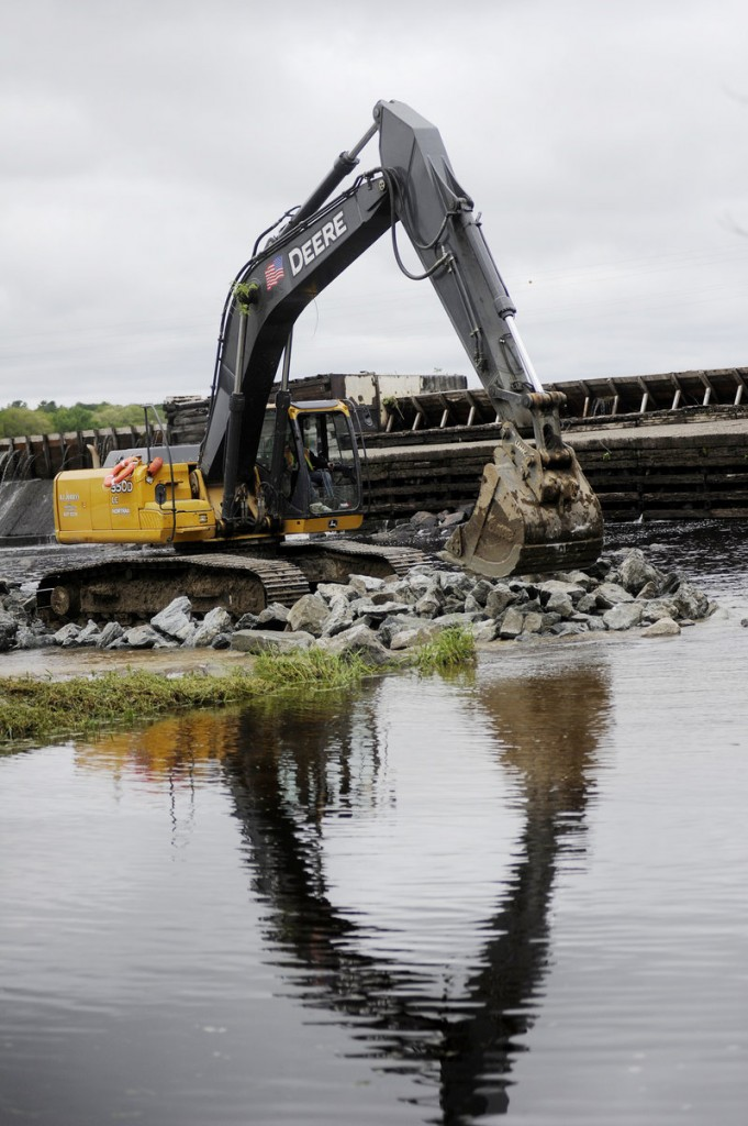 Workers move rocks last week as they build an access road to the Great Works Dam on the Penobscot River. The dam's demolition, starting Monday, is part of a river restoration project that will include removal of the Veazie Dam.