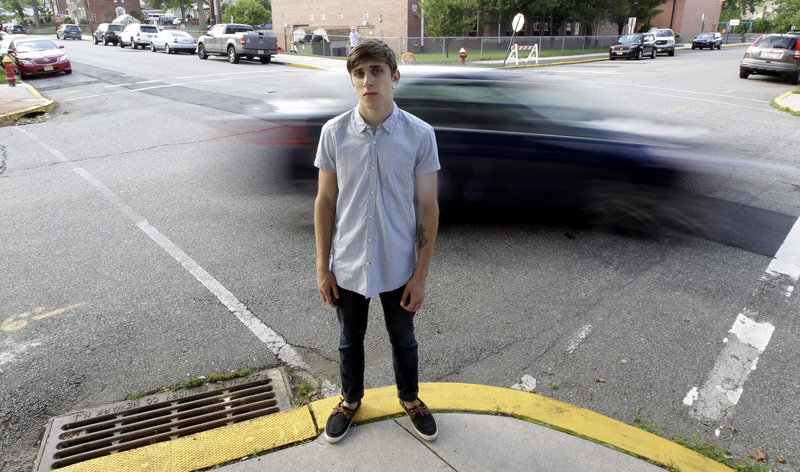 """A vehicle cruises by Dylan Young, 18, in North Arlington, N.J., this week. Young, a high school senior, was in a minor accident caused by being distracted while texting and driving. He said it taught him """"to be a lot more cautious,"""" but he admitted he sometimes still texts behind the wheel. """"Nothing seems to stop them. It's ridiculous,"""" his mother said."""