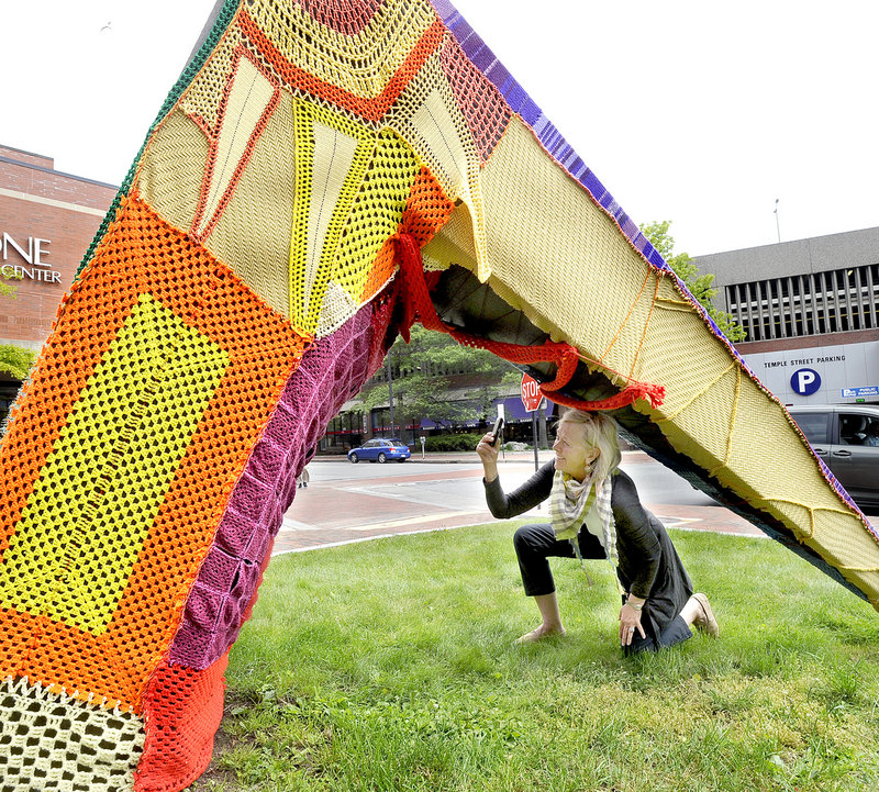 Jean Barash of Wilson, Wyo., takes a photo of a sculpture outside One City Center in Portland on Friday. It was covered in yarn as a prelude to International Yarn Bombing Day today.