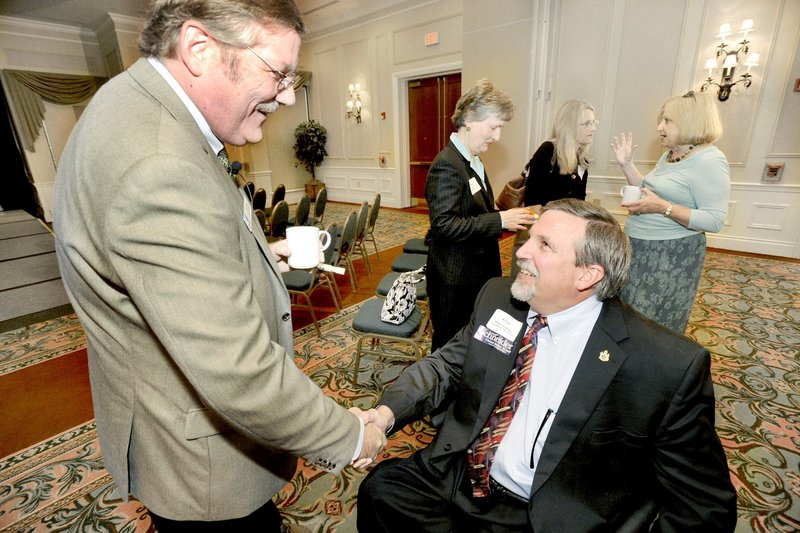 """Attorney General William Schneider, right, a candidate for the GOP nomination for the U.S. Senate, greets Chris Hall at a forum last month. Schneider's political convictions and record in public service """"distinguish him as a leader,"""" a reader says."""