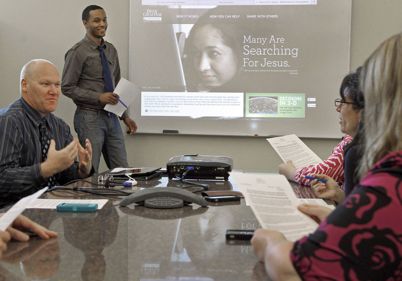 David Arrington, standing, and John Cass, left, talk about the Search for Jesus home page during a team meeting at the Billy Graham Evangelical Association's headquarters in Charlotte, N.C. Critics wonder if it will get lost in the crowd of other similar sites.