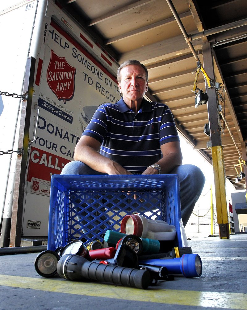 Salvation Army distribution facility production manager Jon Bierd shows banned flashlights on the receiving docks of the Salvation Army distribution facility in Phoenix.