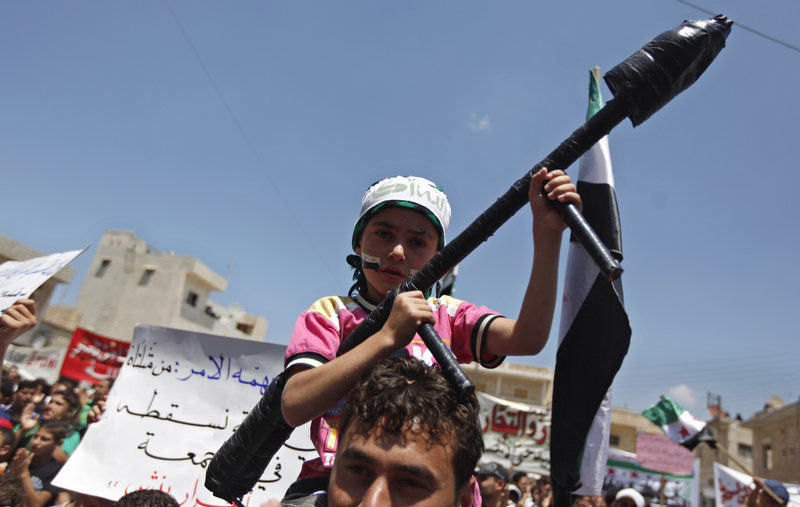 A Syrian boy carries a toy rocket launcher during an anti-Bashar Assad protest on the outskirts of Idlib, Syria, Friday.
