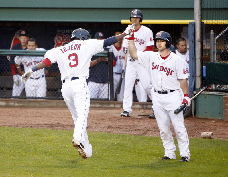 Oscar Tejeda of the Portland Sea Dogs is welcomed by Dan Butler after hitting a solo home run in the second inning Friday night. Portland went on to beat the Richmond Flying Squirrels 4-1 at Hadlock Field.