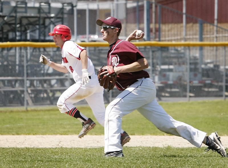 Windham pitcher Nate Boyle throws home for an out while Scarborough's Aaron Ravin heads to third base during their Western Class A semifinal Saturday. Scarborough avenged two regular-season losses to the Eagles, winning 7-0 to advance to the regional final against Cheverus.