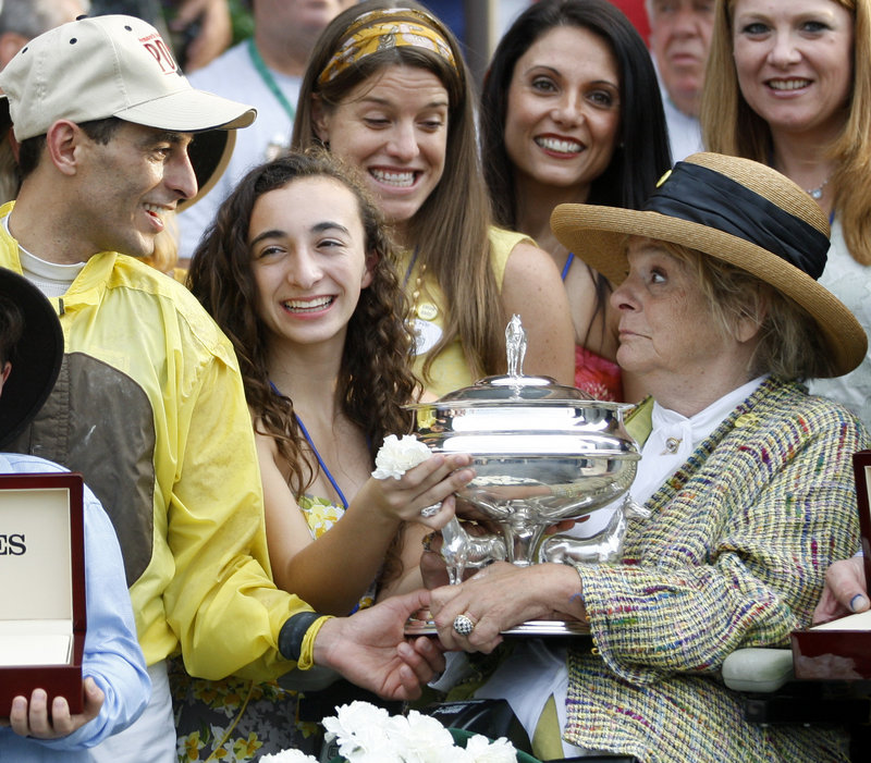 Phyllis Wyeth, right, the owner of Union Rags, is handed the winning trophy Saturday by jockey John Velazquez after Union Rags captured the Belmont Stakes. Wyeth is a part-time resident of Tenants Harbor, Maine.