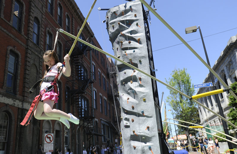 Seven-year-old Sophia Tanguay of Waterboro jumps on the Maine Rock Gym's Extreme Air Jumper during the Old Port Festival.