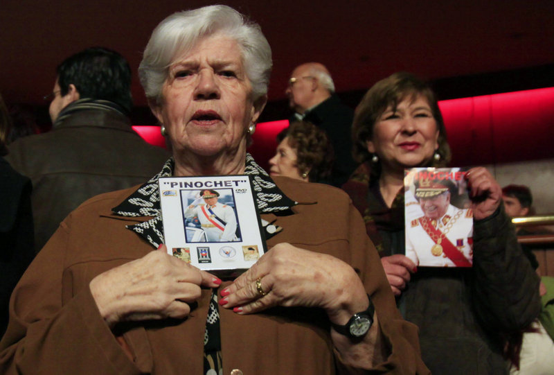Supporters hold pictures of Pinochet at the screening of a pro-Pinochet documentary Sunday. Loyalists say Pinochet saved Chile from communism and was a victim of vengeful leftists who accused him of human rights abuses.