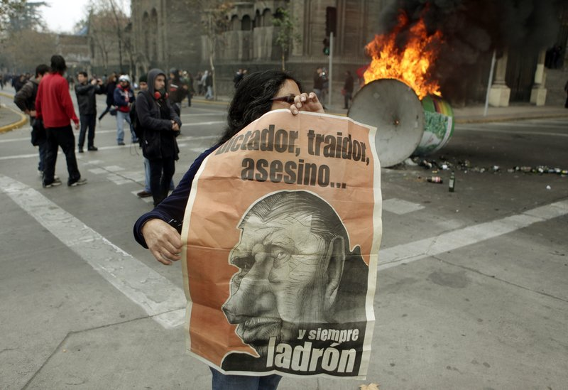 """A woman holds a poster depicting Gen. Augusto Pinochet, who governed Chile from 1973 to 1990, during a protest Sunday in Santiago, Chile, at the premiere of a pro-Pinochet documentary. The writing reads in Spanish: """"Dictator, traitor, killer ... and always thief."""""""