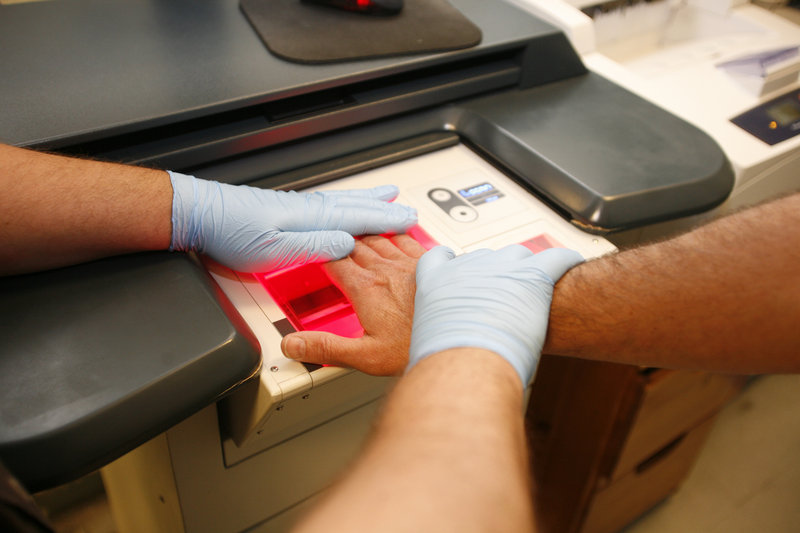 A booking officer scans a palm in the intake area at the Cumberland County Jail in Portland last week.