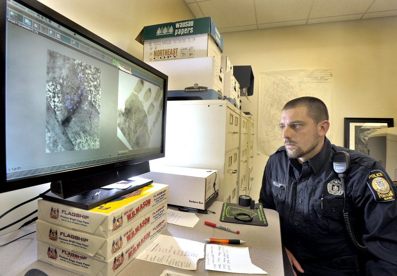 Portland Police Department evidence technician Frank Pellerin examines a palm print on his computer monitor.