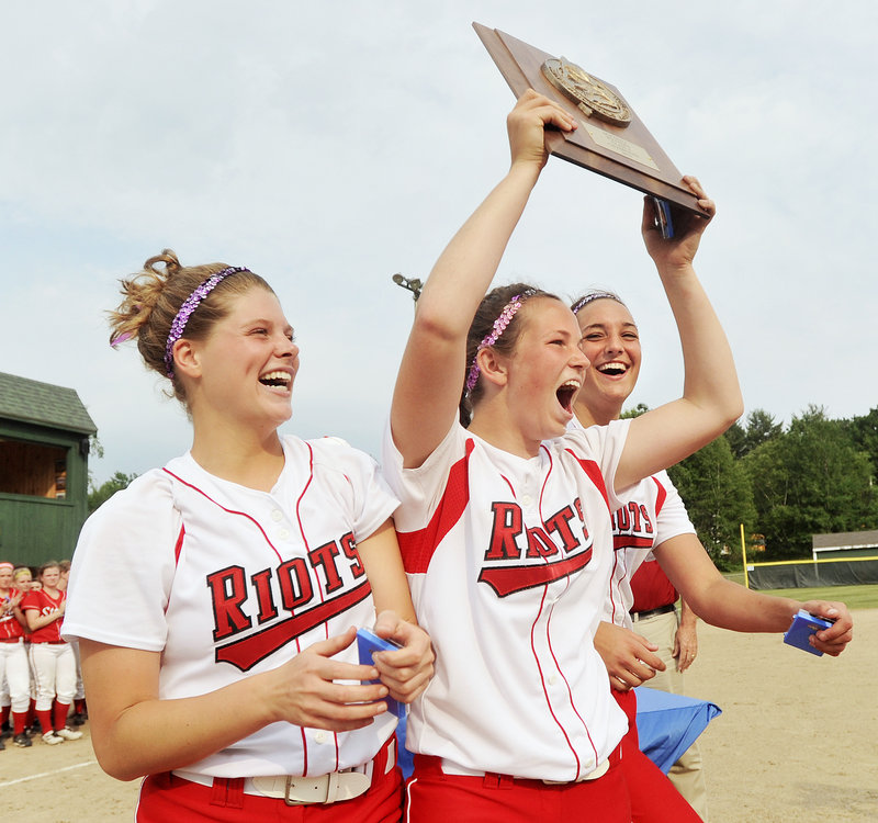 Danica Gleason, center, flanked by Libby Grant, left, and Erin Bogdanovich – the three captains for the South Portland softball team – raises the plaque Tuesday after the Red Riots won the Western Class A softball title with a 5-1 victory against Scarborough.
