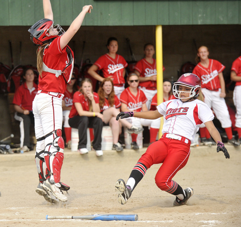 Laurine German of South Portland ties the game, scoring on a single by Olivia Indorf – the first run of a five-run sixth inning that gave the Red Riots a 5-1 victory in the Western Class A final Tuesday. The Scarborough catcher is Abbie Sweatt.