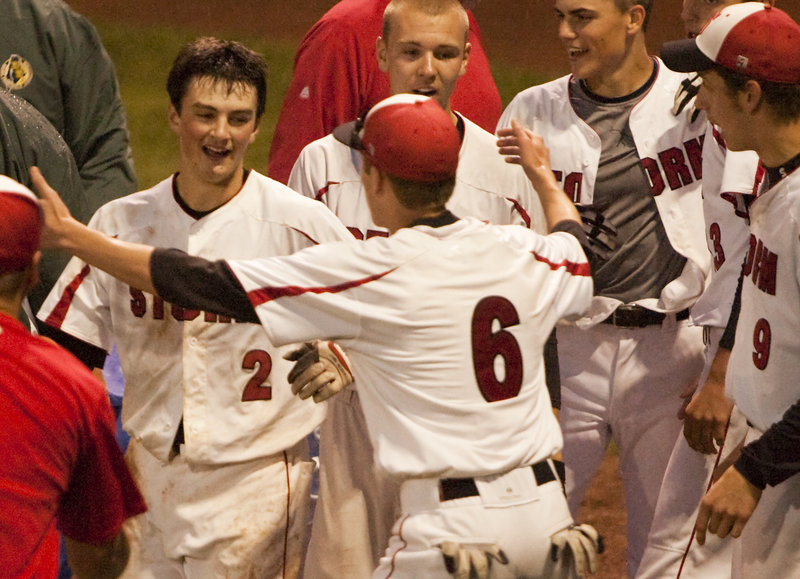 Joe Cronin is welcomed by his Scarborough teammates Tuesday night after his two-run homer in the seventh inning provided a 7-5 victory against Cheverus and the Western Class A baseball title.