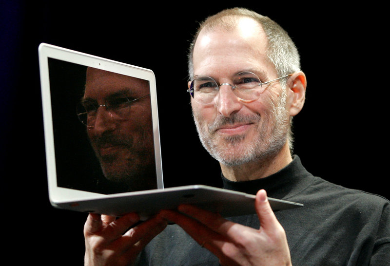 In this 2008 photo, Apple CEO Steve Jobs holds up the new MacBook Air after giving the keynote address at the Apple MacWorld Conference in San Francisco.